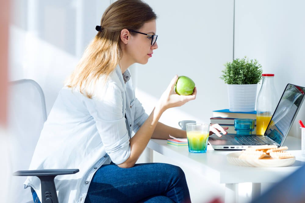 Woman eating apple in front of computer